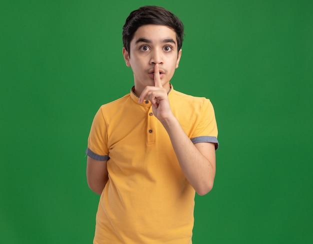 Ragazzo impressionato che guarda davanti facendo gesto di silenzio nascondendo la mano dietro la schiena isolata sul muro verde con spazio per le copie