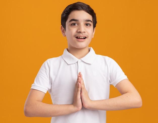 Ragazzo impressionato che guarda davanti tenendo le mani insieme isolate sul muro arancione