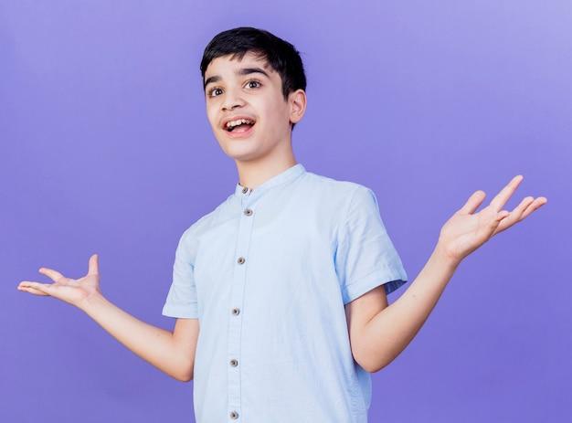 Ragazzo giovane impressionato che guarda al lato che mostra le mani vuote isolate sulla parete viola