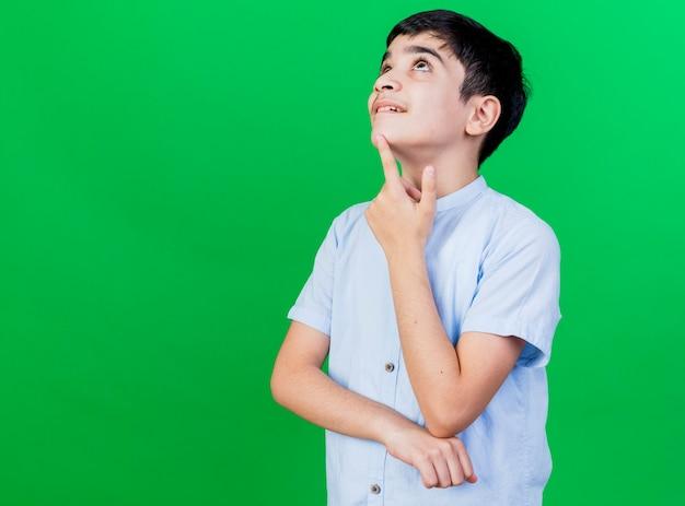 緑の壁に孤立して見上げるあごに指を置く感動の少年