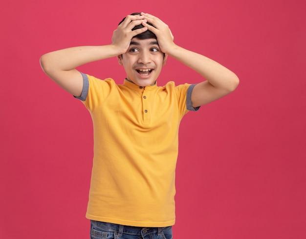 Ragazzo impressionato che mette le mani sulla testa guardando il lato isolato sul muro rosa