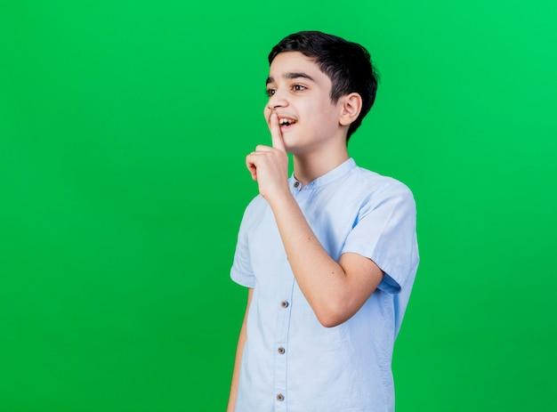 緑の壁に分離された沈黙のジェスチャーをしているまっすぐに見える縦断ビューに立っている感動の少年