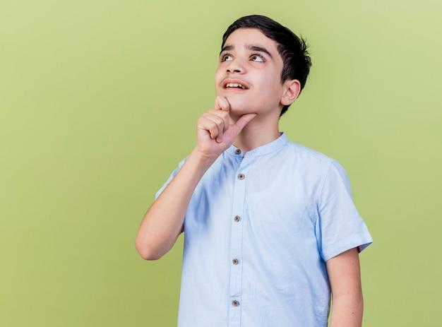 オリーブグリーンの壁に孤立して見上げるあごに触れて感動した少年