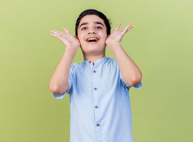 올리브 녹색 벽에 고립 된 전면을보고 빈 손을 보여주는 얼굴을 만지고 감동 어린 소년 무료 사진