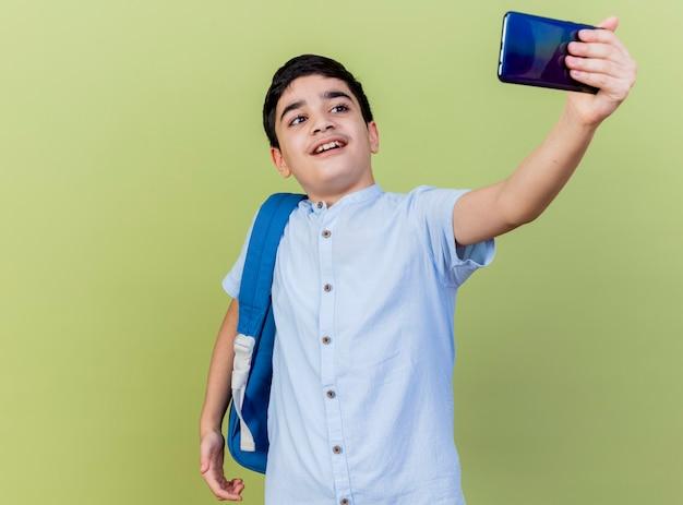 オリーブグリーンの壁に隔離されたselfieを取っているバックバッグを身に着けている感動の少年