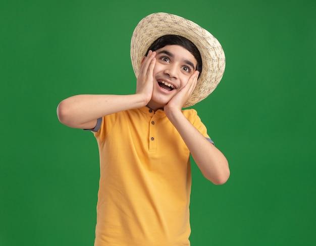 コピースペースで緑の壁に孤立してまっすぐに見える顔に手を置いてビーチ帽子をかぶっている感動の少年
