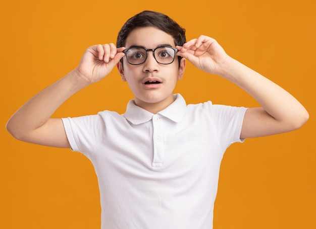 Impressionato ragazzo che indossa e afferra gli occhiali guardando dritto isolato sul muro arancione