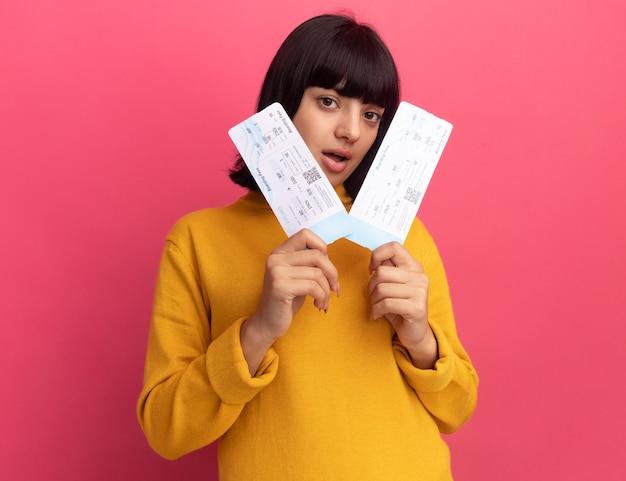 La giovane ragazza caucasica castana impressionata tiene i biglietti aerei isolati sulla parete rosa con lo spazio della copia