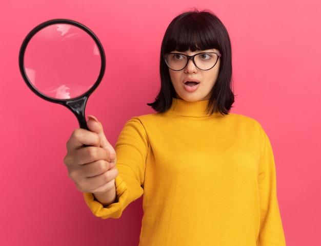 La giovane ragazza caucasica castana impressionata in vetri ottici tiene e guarda la lente d'ingrandimento isolata sulla parete rosa con lo spazio della copia