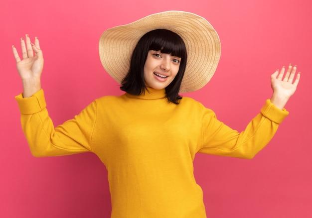 ピンクの上げられた手でビーチ帽子をかぶっている感動の若いブルネット白人の女の子