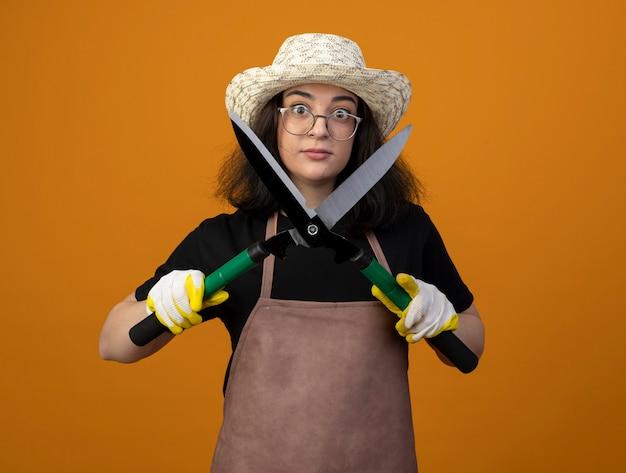 Впечатленная молодая брюнетка женщина-садовник в оптических очках и в униформе в садовой шляпе и перчатках держит садовые ножницы, изолированные на оранжевой стене с копией пространства