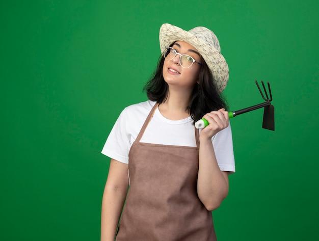 光学ガラスと制服を着たガーデニング帽子で感銘を受けた若いブルネットの女性の庭師は、緑の壁に分離されたくわ熊手を保持します