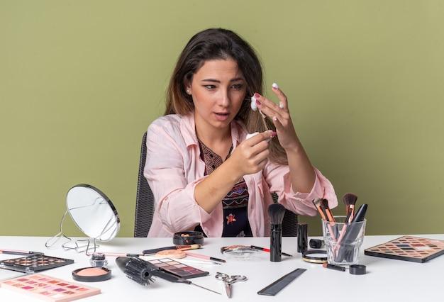 Впечатленная молодая брюнетка девушка сидит за столом с инструментами для макияжа, применяя мусс для волос