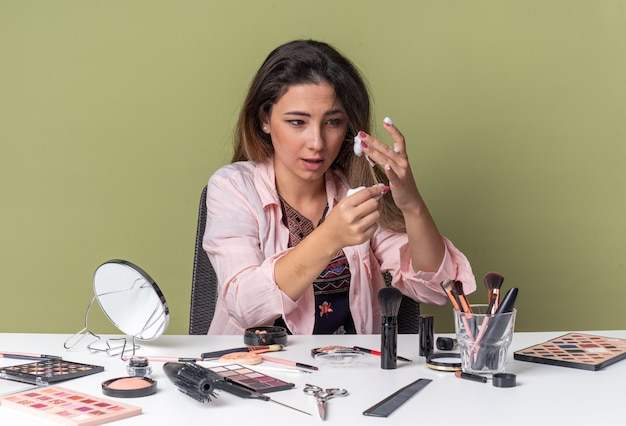 Impressionata giovane ragazza bruna seduta al tavolo con strumenti per il trucco che applicano mousse per capelli