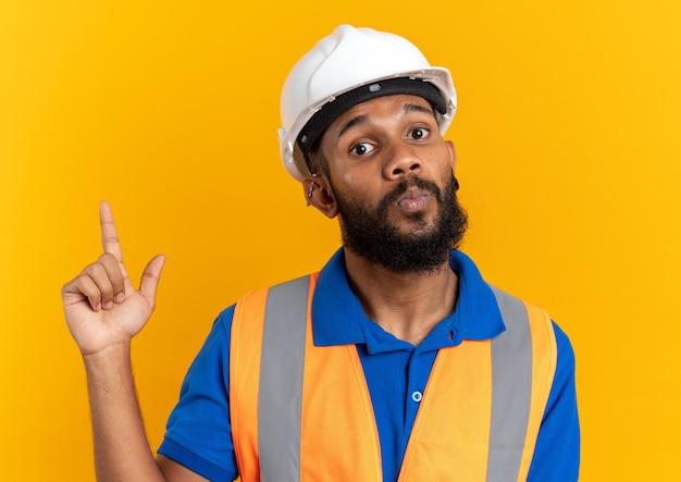 복사 공간이 있는 주황색 벽에 고립되어 있는 안전 헬멧을 쓴 제복을 입은 젊은 건축업자에게 깊은 인상을 받았습니다.