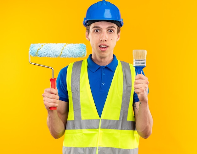 Impressed young builder man in uniform holding roller brush with paint brush
