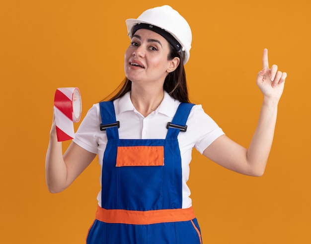 Впечатленная молодая женщина-строитель в униформе, держащая изоленту указывает вверх, изолированную на оранжевой стене