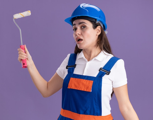 紫色の壁に分離されたミニペイントローラーを保持している制服を着た若いビルダーの女性に感銘を受けました