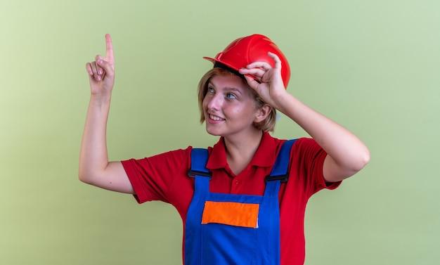 Impressionato giovane donna costruttore in uniforme punta verso l'alto isolato su muro verde oliva
