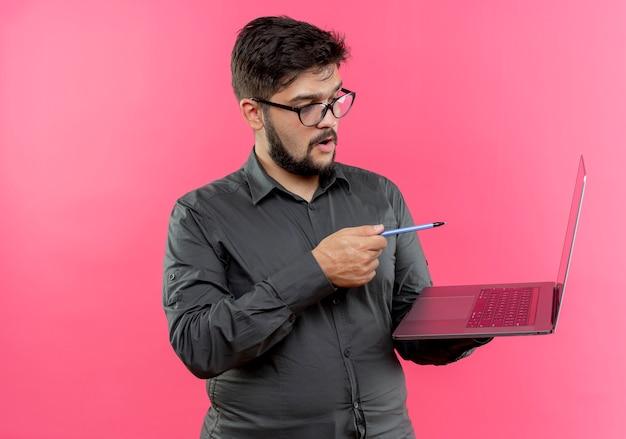 Impressionato giovane uomo d'affari con gli occhiali che tengono e punti con la penna al computer portatile isolato sulla parete rosa