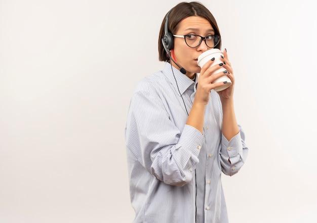 コピースペースで白で隔離された側を見てプラスチック製のコーヒーカップからコーヒーを飲む眼鏡とヘッドセットを身に着けている感動の若いコールセンターの女の子