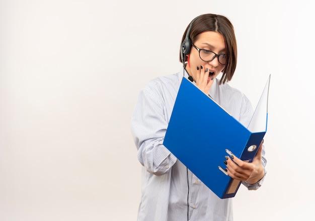 眼鏡とヘッドセットを持って、コピースペースで白で隔離された口に手を置いてフォルダーを見て感動した若いコールセンターの女の子