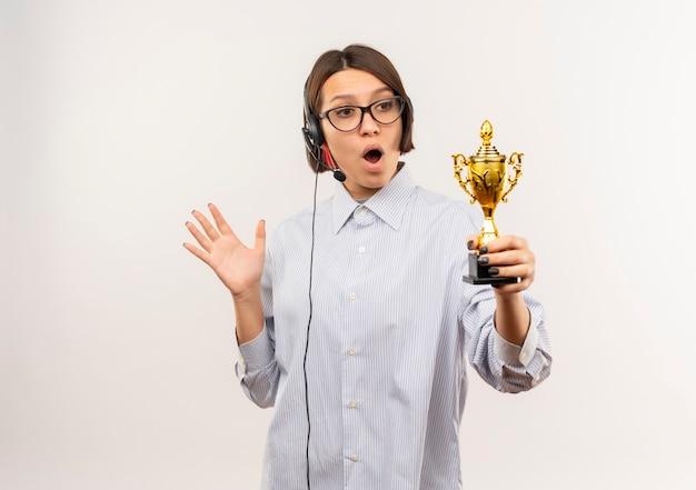 眼鏡とヘッドセットを身に着けて勝者のカップを保持し、見て、コピースペースで白で隔離された空の手を示している感動の若いコールセンターの女の子