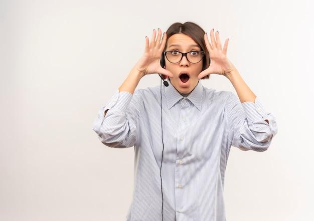 Impressionato giovane ragazza della call center con gli occhiali e auricolare mantenendo le mani vicino al viso isolato su bianco con spazio di copia