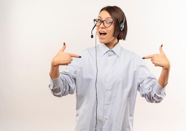 Impressionato giovane ragazza della call center con gli occhiali e auricolare che punta a se stessa isolato su bianco con spazio di copia