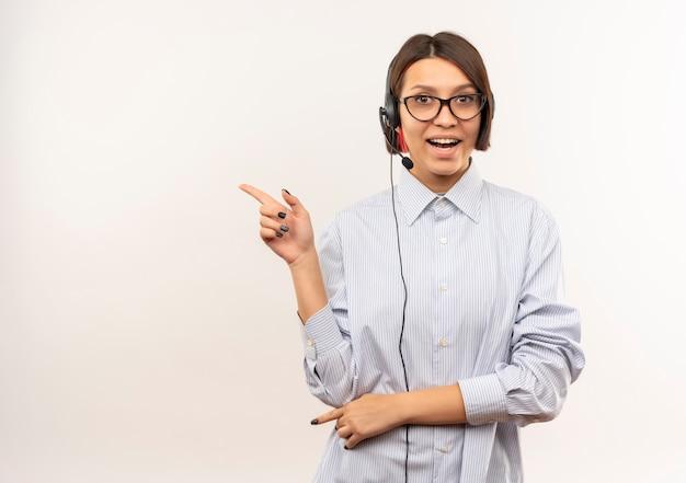 Impressionato giovane ragazza della call center con gli occhiali e auricolare rivolto verso il lato isolato su bianco con spazio di copia