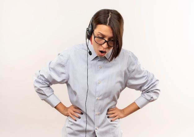 Impressionato giovane ragazza della call center con gli occhiali e auricolare mettendo le mani sulla vita guardando verso il basso isolato su bianco con lo spazio della copia