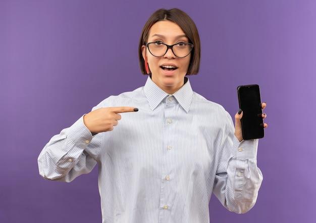 Впечатлила молодая девушка колл-центра в очках, держащая и указывая на мобильный телефон, изолированный на фиолетовом