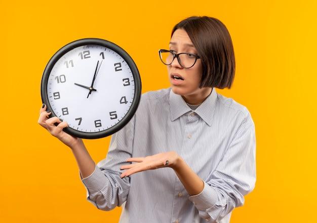 オレンジ色に分離された手で時計を見て、指している眼鏡をかけている感動の若いコールセンターの女の子