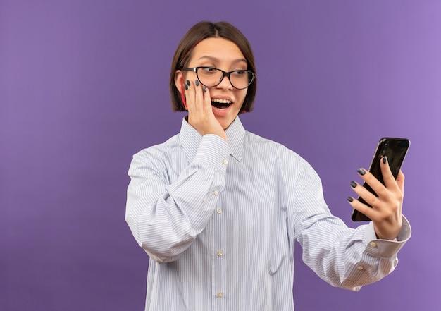 Impressionato giovane ragazza della call center con gli occhiali tenendo e guardando il telefono cellulare con la mano sul viso isolato su viola con spazio di copia