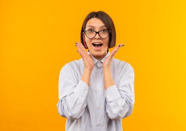 Impressionato giovane ragazza della call center con gli occhiali che tengono le mani vicino al viso isolato sull'arancio con lo spazio della copia