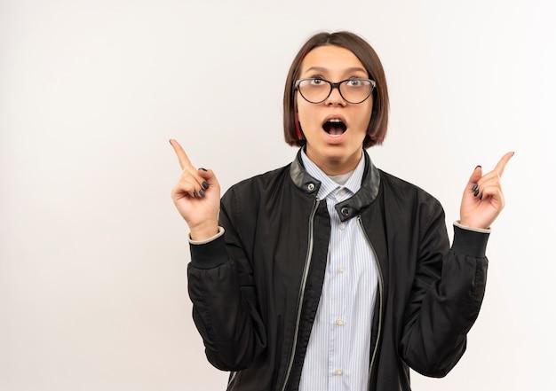 Impressionato giovane ragazza della call center con gli occhiali alla ricerca e rivolto verso l'alto isolato su bianco con spazio di copia