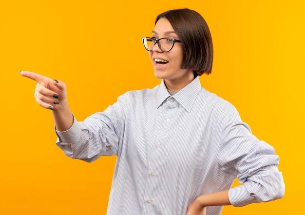 オレンジ色に分離された側を見て、腰に手を置いて眼鏡をかけている感動の若いコールセンターの女の子