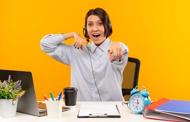 オレンジ色に分離された机を指して彼女の手に座っているヘッドセットを身に着けている感動の若いコールセンターの女の子