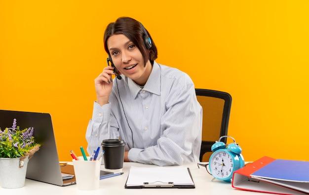 オレンジ色に分離されたヘッドセットに手を置いて机に座っているヘッドセットを身に着けている感動の若いコールセンターの女の子