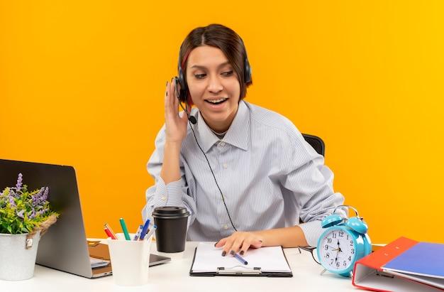 オレンジ色に分離された側を見てヘッドセットに手を置いて机に座っているヘッドセットを身に着けている感動の若いコールセンターの女の子