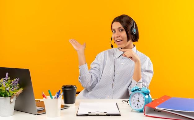 机に座って空の手を示し、オレンジ色に分離されたそれを指しているヘッドセットを身に着けている感動の若いコールセンターの女の子