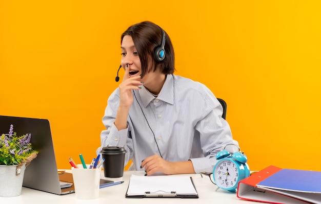 Impressionato giovane ragazza della call center che indossa la cuffia avricolare che si siede allo scrittorio che esamina il computer portatile con il dito sulle labbra isolate sull'arancio