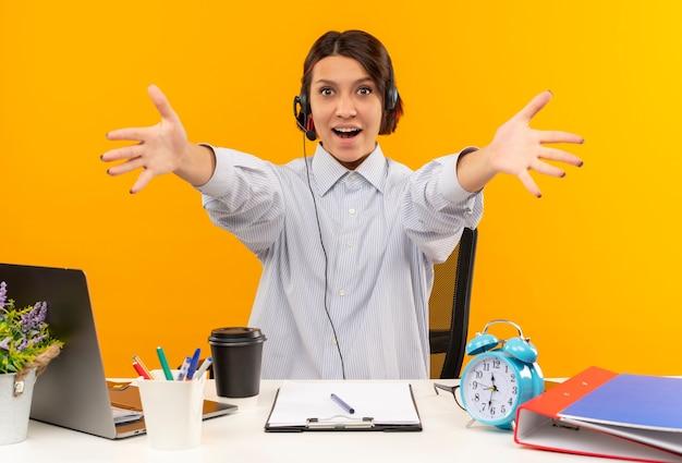 Impressionato giovane ragazza della call center che indossa la cuffia avricolare che si siede allo scrittorio che allunga le mani verso la macchina fotografica isolata sull'arancio