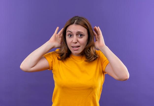 孤立した紫色の空間で耳の近くの手でジェスチャーをしている感動の若いカジュアルな女性