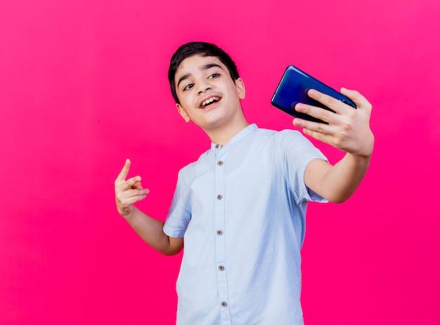 Впечатленный молодой кавказский мальчик делает знак мира, делающий селфи на малиновом фоне с копией пространства