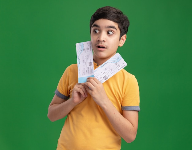 Impressed young caucasian boy holding airplane tickets looking at side