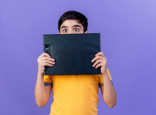 コピースペースで紫色の壁に分離されたクリップボードを後ろから保持している印象的な若い白人の少年