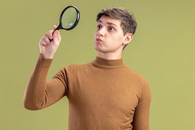 Impressed young caucasian boy holding and looking at magnifying glass