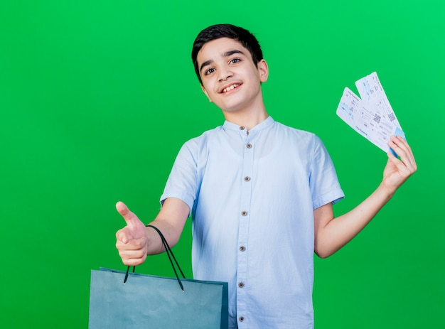 緑の壁に隔離された親指を表示して買い物袋と飛行機のチケットを保持している印象的な若い白人の少年