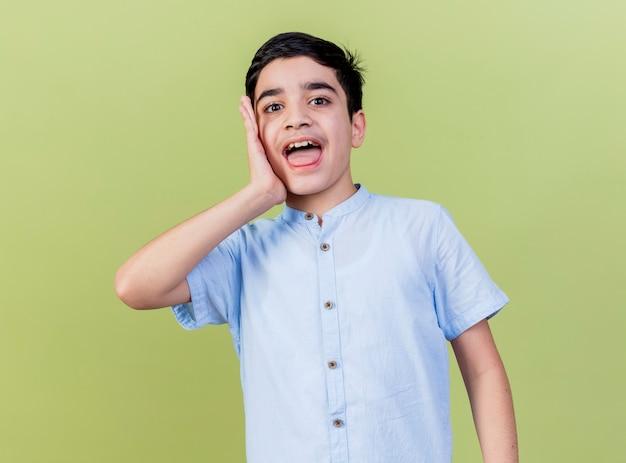 Impressionato giovane ragazzo caucasico tenendo la mano sul viso isolato sulla parete verde oliva